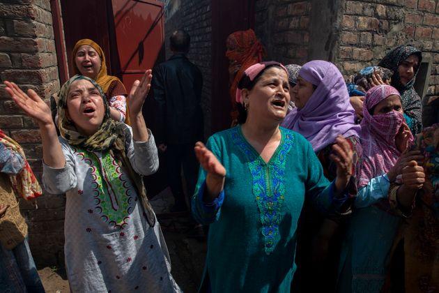 Kashmiri women grieve near the residential buildings damaged during a gun battle in Srinagar, Jammu and...