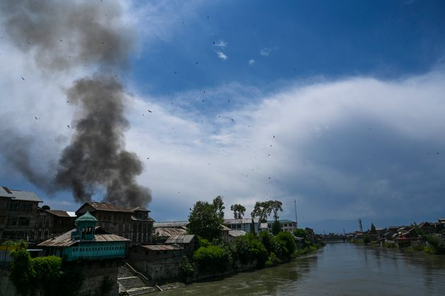 Smoke rises from a house at a site of a gun battle between militants and government forces in Srinagar,...