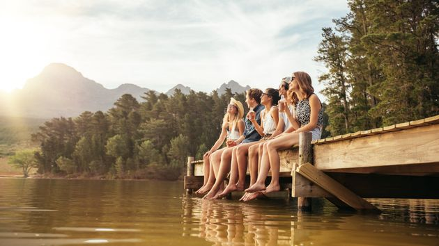 Portrait of relaxed young people sitting on the jetty with beers. Friends hanging out at the lake on...