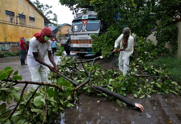 Rescue workers cut tree branches that fell on a truck trailer after heavy winds caused by Cyclone Amphan,...