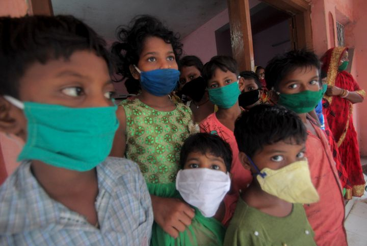 Evacuated children wearing masks as a precaution against the spread of coronavirus stand at a relief camp at Paradeep, on the