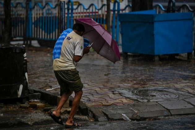 A man struggles to hold his umbrella and walk against high wind in Kolkata, Wednesday, May 20,