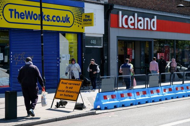 A road in north London is narrowed to aid social distancing while shoppers queue for a