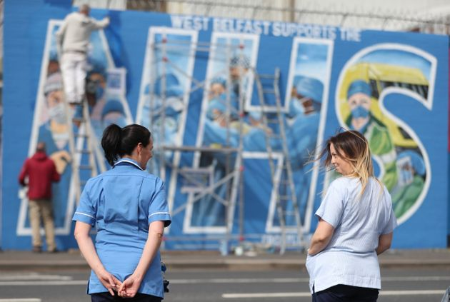 Nurses watch as a mural is painted in recognition of the NHS on the Falls Road in Belfast, as the UK...