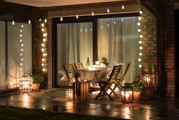 Summer evenig terrace with candles, wine and lights, wet