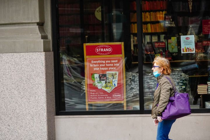 "A pedestrian passes the closed doors of The Strand, an indie bookstore in New York City. A sign in the window advertises ""eve"