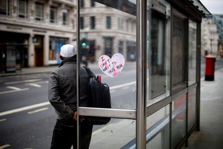 "A sticker reading ""I can't wait to hug you"" is pictured as a man waits at a bus stop in central London."