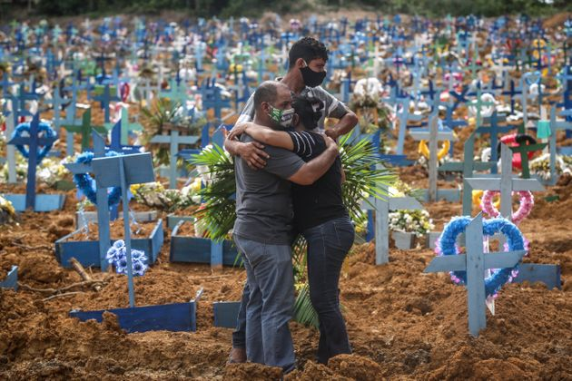 People mourn during a mass burial of coronavirus pandemic victims on May 19, 2020, in Manaus, Brazil....