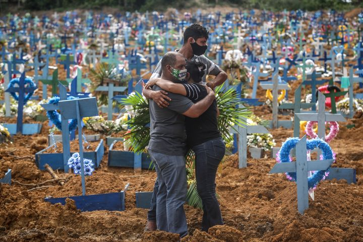 People mourn during a mass burial of coronavirus pandemic victims on May 19, 2020, in Manaus, Brazil. Brazil has over 270,000 confirmed COVID-19 cases and more than 17,000 deaths caused by the virus.