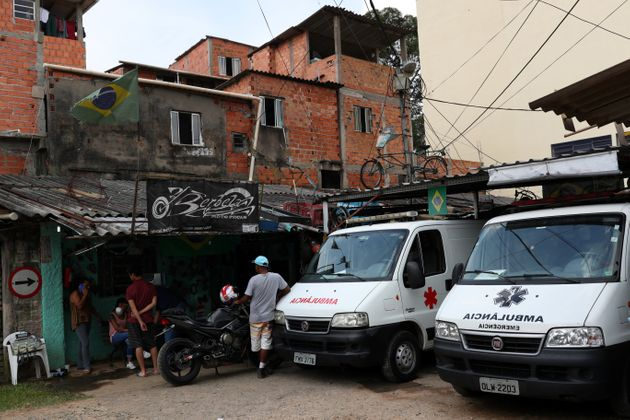 People gather next to ambulances on March 29, 2020, after residents of São Paulo's biggest favela,...