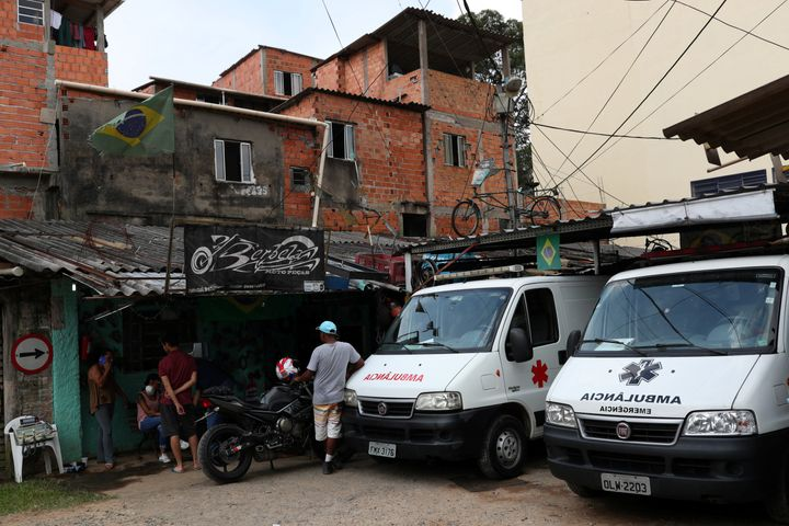People gather next to ambulances on March 29, 2020, after residents of São Paulo's biggest favela, Paraisópolis, hired an around-the-clock private medical service to fight COVID-19.