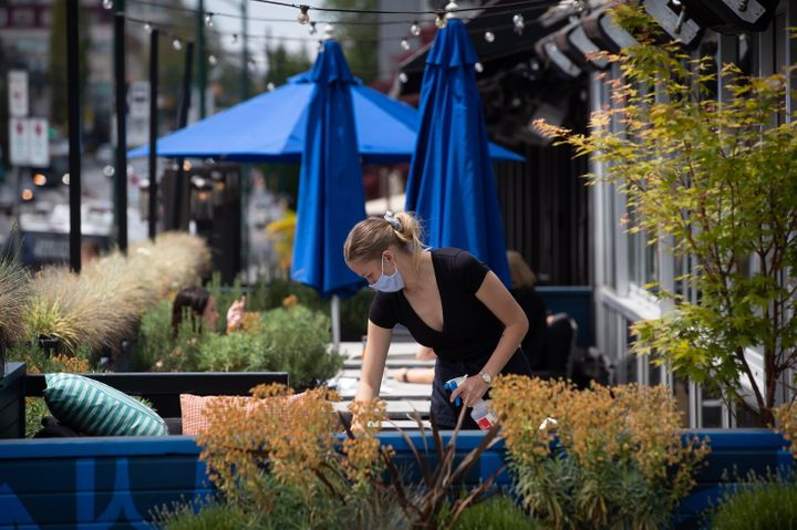 A server wears a face mask while cleaning a table on the patio at an Earls restaurant in Vancouver on May 19, 2020.