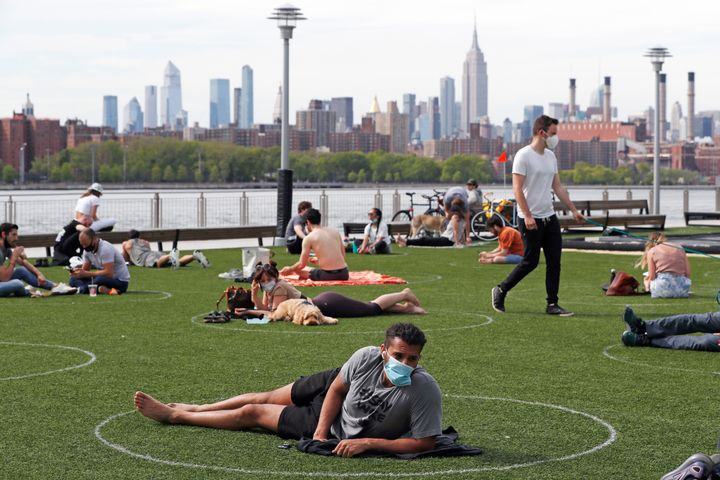 People relax in circles drawn to help social distancing at Domino Park in Brooklyn, New York.