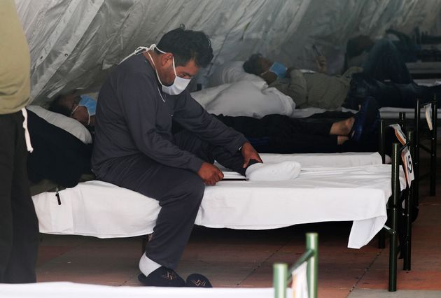 Men diagnosed with COVID-19 who do not have severe symptoms rest inside a tent designated for male patients,...