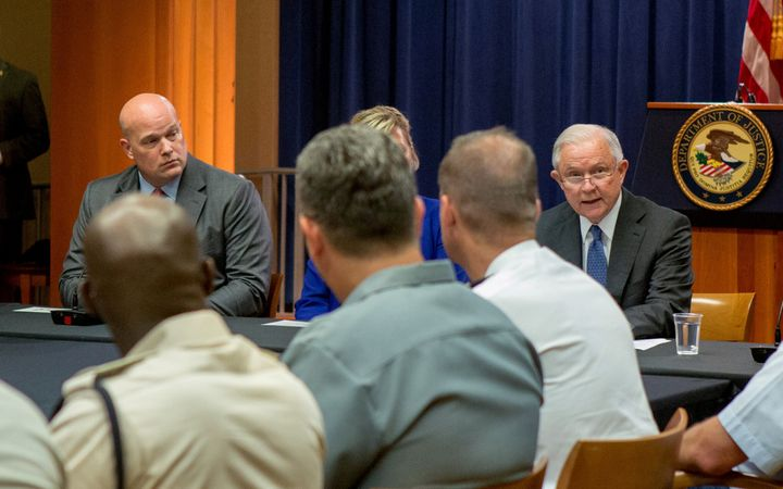Matthew Whitaker looks over at then-Attorney General Jeff Sessions during a roundtable discussion with foreign liaison office