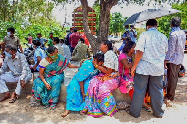 Family members react as they mourn deceased relatives a day after a gas leak incident at LG Polymers...