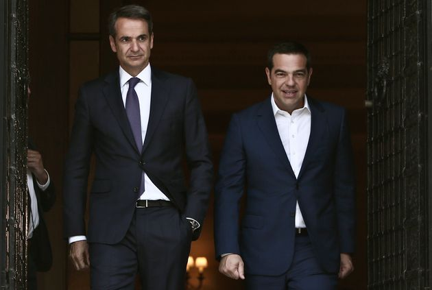 Outgoing Prime Minister Alexis Tsipras (R) exits the Prime Minister's office at Maximos mansion after...