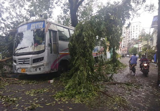 Commuters in Kolkata move past a tree branch precariously hanging over a bus after cyclone Amphan hit...