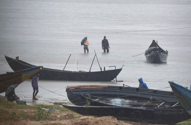 Fishermen are trying to pull their fishing boats back at Talasari beach in heavy wind and rain in Balasore,...