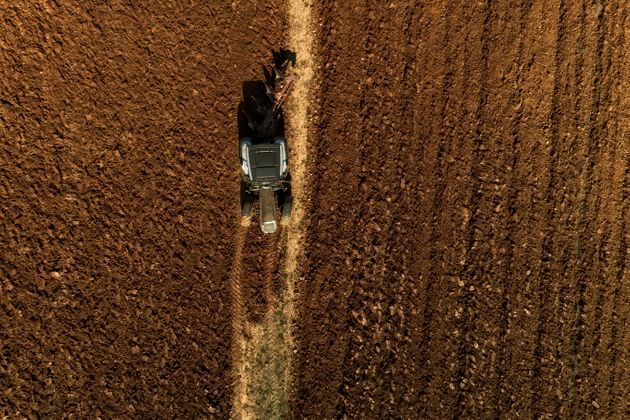 Aerial drone shot of a farmer in tractor seeding, sowing agricultural crops at field in the fertile farm...