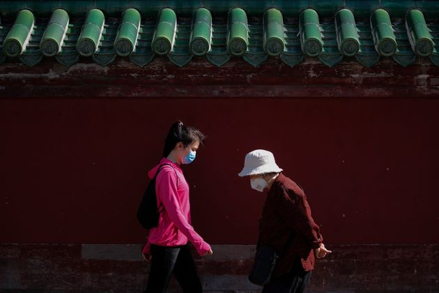 Women wearing protective face masks walk in Beijing, May 10,