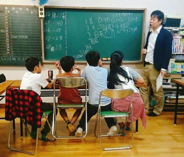 学習支援教室で子どもたちに指導する田口吾郎さん(右)