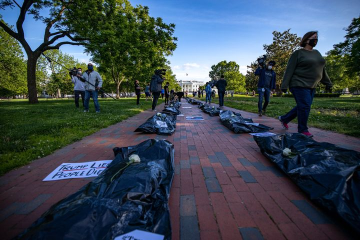 "Signs affixed to body bags read ""Trump Lies, People Die,"" symbolizing the nearly 100,000 people in the U.S."
