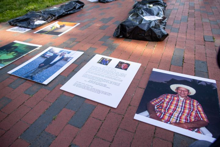 Progressive activists outside the White House in Washington D.C. lay body bags and photos of loved ones killed by the coronav