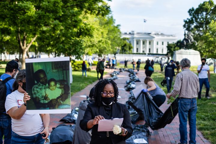 Progressive activists outside the White House in Washington, D.C., lay body bags and photos of loved ones killed by the coron