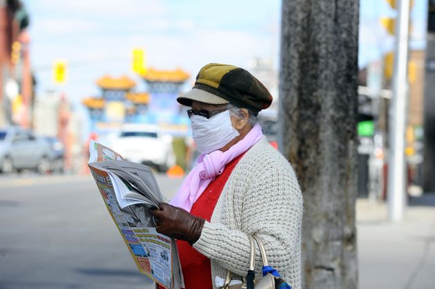 A woman wears a face mask as she reads a newspaper in Ottawa on May 5, 2020. People with hearing impairment...