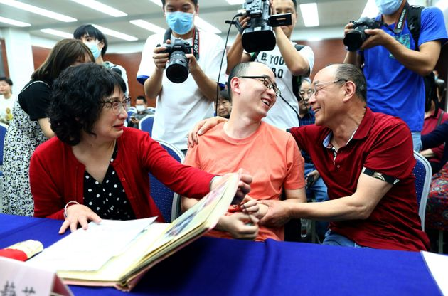 This photo taken on May 18, 2020 shows Mao Yin (C) speaking with his mother Li Jingzhi (L) and father...