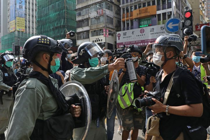A riot police officer points pepper spray at a journalist as pro-democracy activists gather outside a shopping mall during th