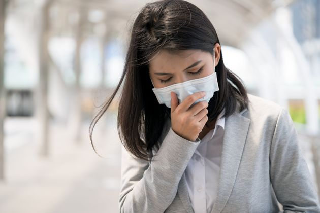 shot of a sickly woman wear protective mask and having cough while walking in