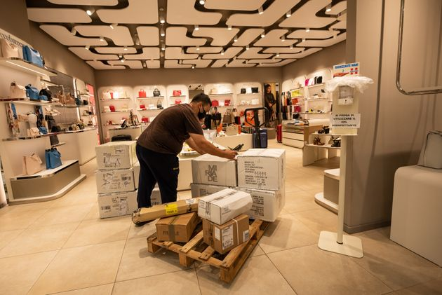 CORIGLIANO-ROSSANO, CALABRIA, ITALY - 2020/05/18: A porter unloads goods in a shop in a mall. From May...