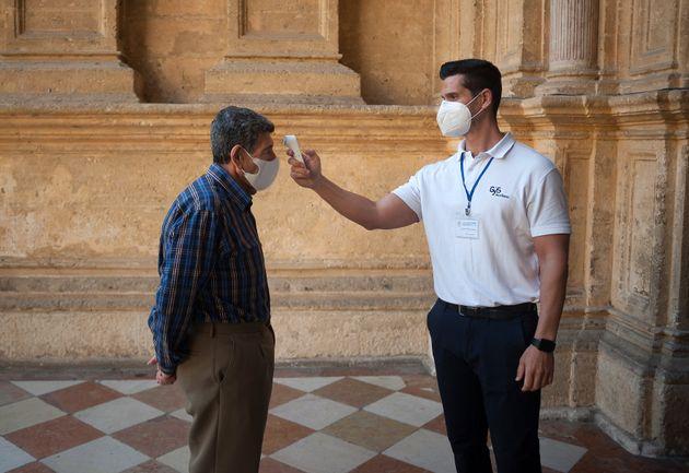 Un trabajador toma la temperatura a un hombre en Málaga durante la