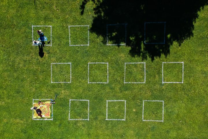 People practice social distancing sitting inside squares painted on a lawn by Vistula Boulevard in Krakow, Poland.