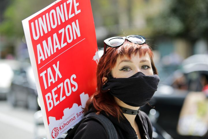 Some Amazon workers have spoken out about working conditions during the pandemic, even though the company is nonunion. Here, a protestor holds a sign at the Amazon Spheres in Seattle on May 1.