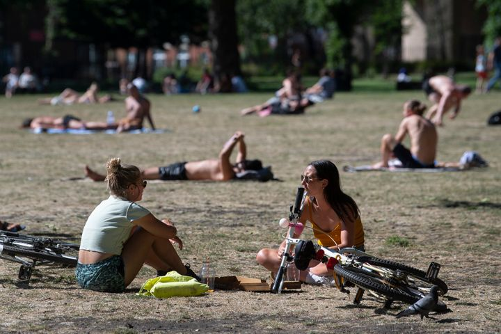 People enjoy the sun in London Fields park in East London.