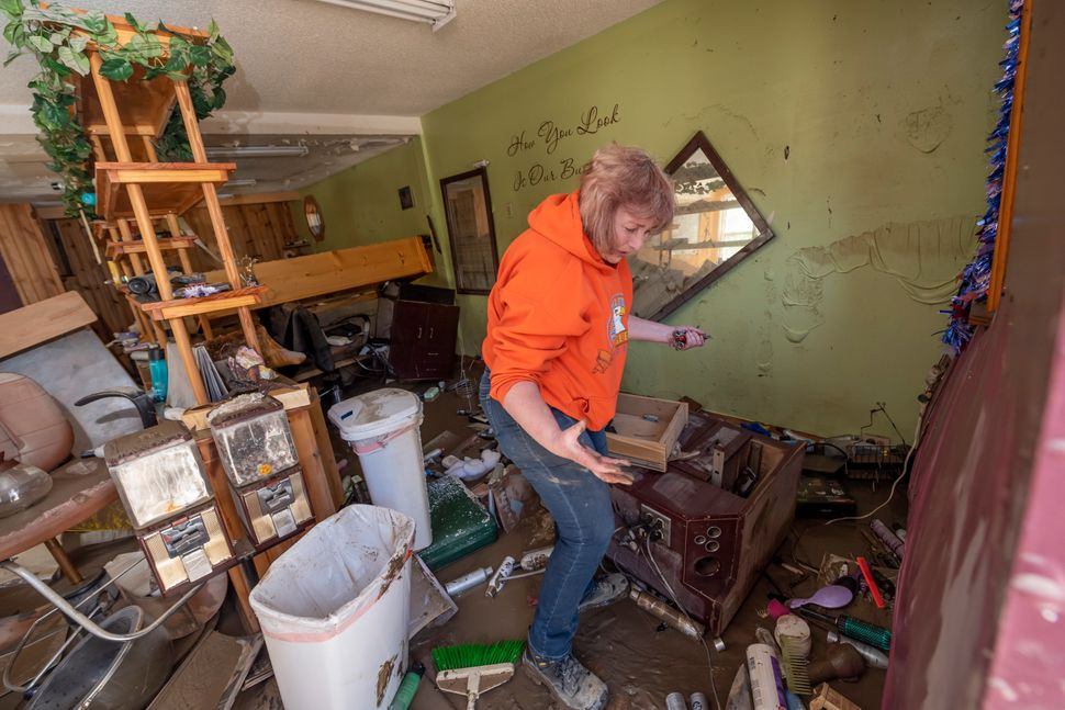 Connie Methner, owner of CJ's Hairstyling, wades through the mud covering the inside of her salon in Sanford, Michigan, on Ma