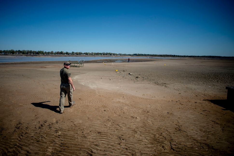 Sanford resident Clint Clark, 44, walks out into what was once the bottom of Wixom Lake after water washed out due to the fai