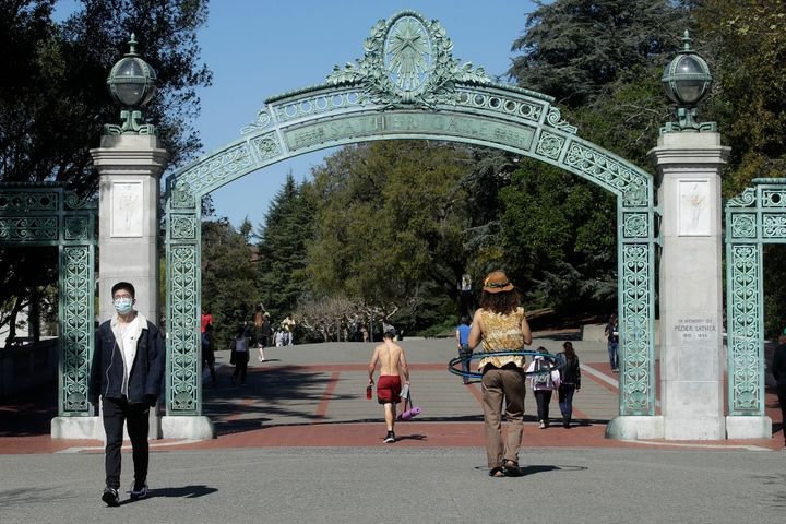 A man wears a mask while walking past Sather Gate on the University of California, Berkeley, campus on March 11, 2020.