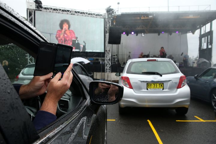 SYDNEY, AUSTRALIA - MAY 21: A man in a car takes a selfie as Casey Donovan performs on stage during a media call to showcase how a drive-in live entertainment venue will operate ahead of its opening in July in the suburb of Tempe on May 21, 2020 in Sydney, Australia.  From July visitors will be able to drive to the venue and enjoy music and performances from the safety of their vehicles as restrictions on group sizes continues due to the COVID-19 pandemic. (Photo by Don Arnold/WireImage)