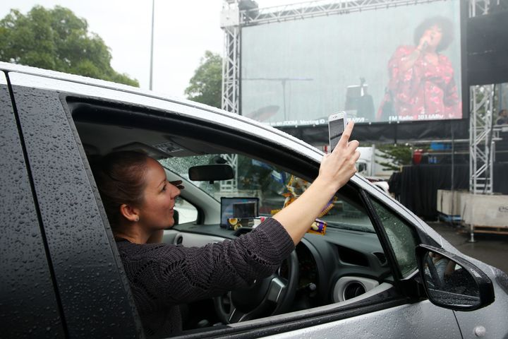 SYDNEY, AUSTRALIA - MAY 21: A girl in a car takes a selfie as Casey Donovan performs on stage during a media call to showcase how a drive-in live entertainment venue will operate ahead of its opening in July in the suburb of Tempe on May 21, 2020 in Sydney, Australia.  From July visitors will be able to drive to the venue and enjoy music and performances from the safety of their vehicles as restrictions on group sizes continues due to the COVID-19 pandemic. (Photo by Don Arnold/WireImage)