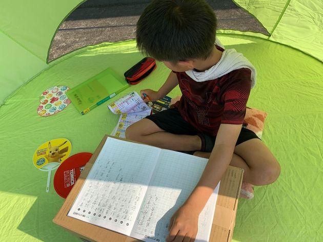 「自宅のテーブルだと集中できないため、気分を変えてルーフバルコニーにテントを広げ、ダンボールを机がわりに学校の課題に取り組んでいます」(小4の息子を持つ女性)