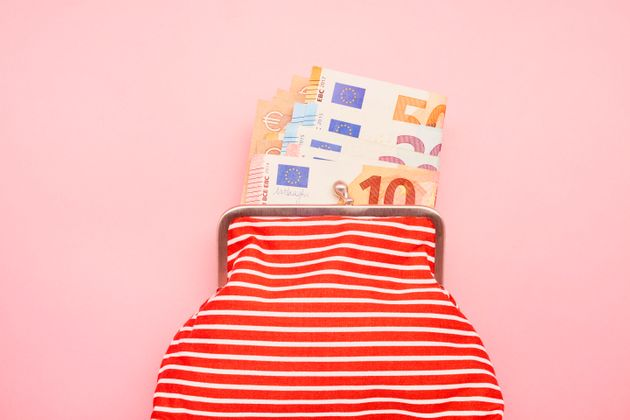 Directly above shot of a wallet and Euro banknotes on pink background