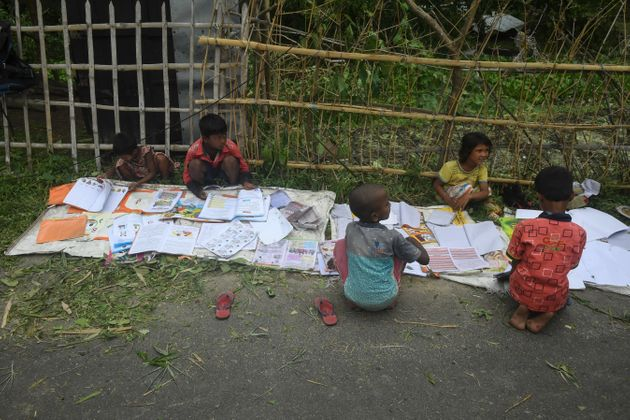 Children lay out their wet textbooks to dry following the landfall of cyclone Amphan in Khejuri area...