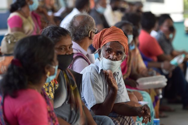 A migrant worker from Tamil Nadu waits to be screened along with other workers before travelling in a...
