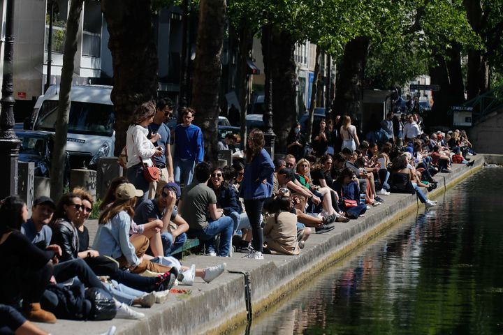 People sit on a bank of the Canal Saint-Martin in Paris, on May 16, 2020, on the first weekend after France eased lockdown me