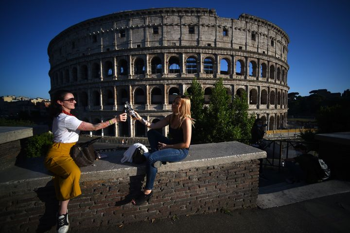 Young women share an aperitif drink by the Colosseum in Rome on May 21, 2020, after the country eases its two-month lockdown.