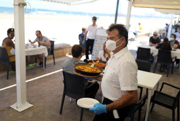 Un camarero en un restaurante en Valencia llevando
